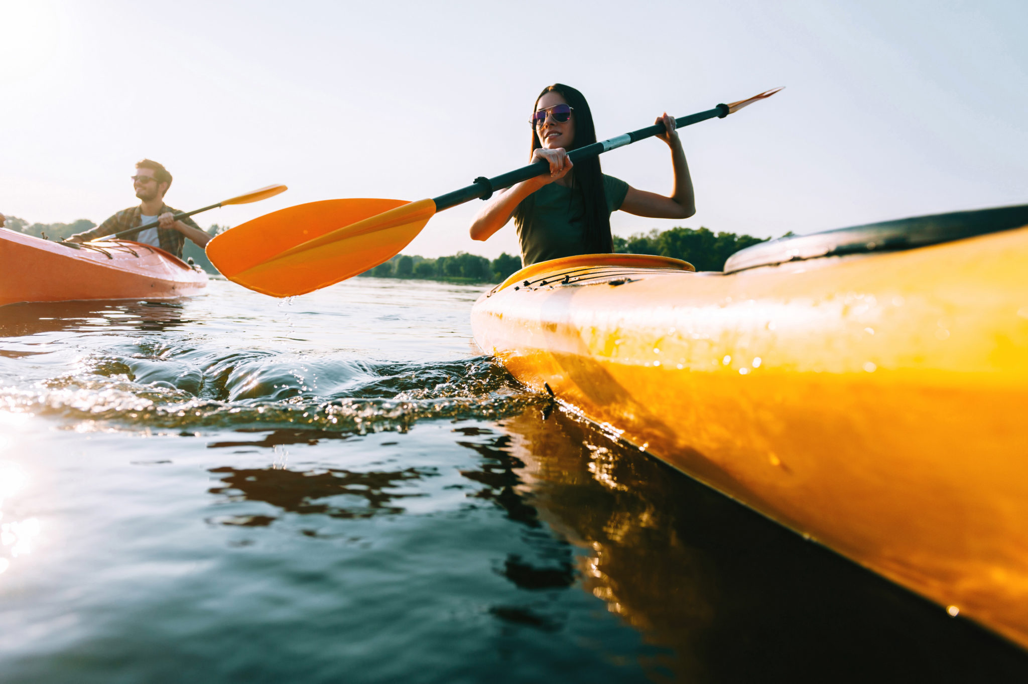 Couple kayaking. Low angle view of beautiful young couple kayaking on lake together and smiling